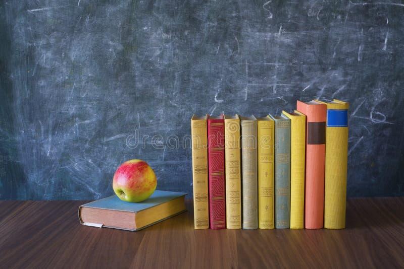 Fila de libros y de una manzana imagenes de archivo