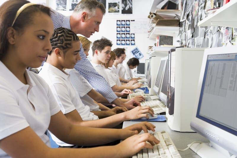 Fila de los alumnos que estudian en los ordenadores imagen de archivo libre de regalías
