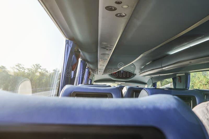 Fila de los asientos azules vacíos en autobús del coche, día soleado detrás de la ventana, visión desde fotos de archivo
