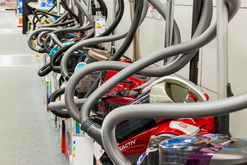 Fila de los aspiradores de diversos fabricantes en la tienda de dispositivos Venta del equipo eléctrico del hogar en imagen de archivo