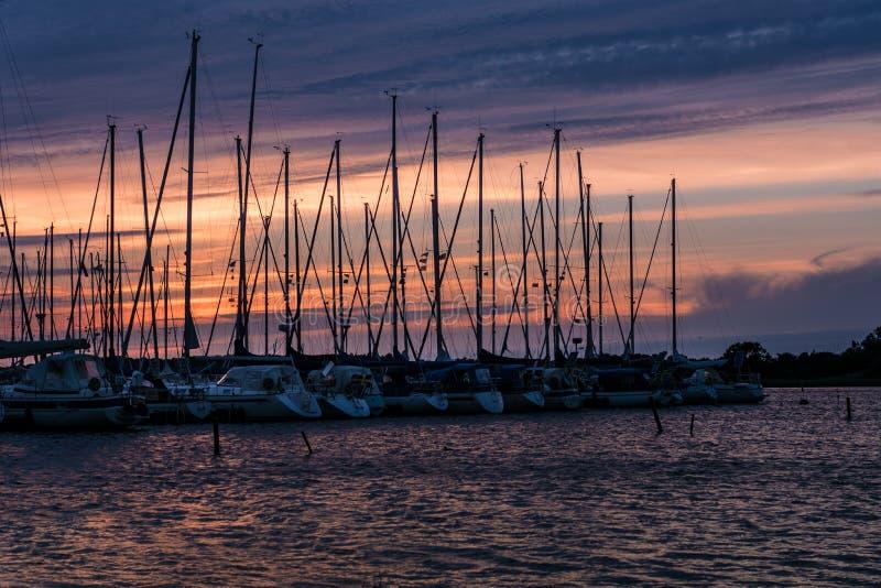 Fila de los barcos de navegación anclados en luz del sol rosada de la tarde imagen de archivo