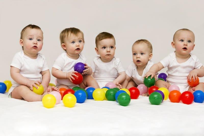Fila de los bebés caucásicos que sientan de lado a lado parecer lejos aislado en fondo gris Cinco bebés lindos que juegan con foto de archivo libre de regalías