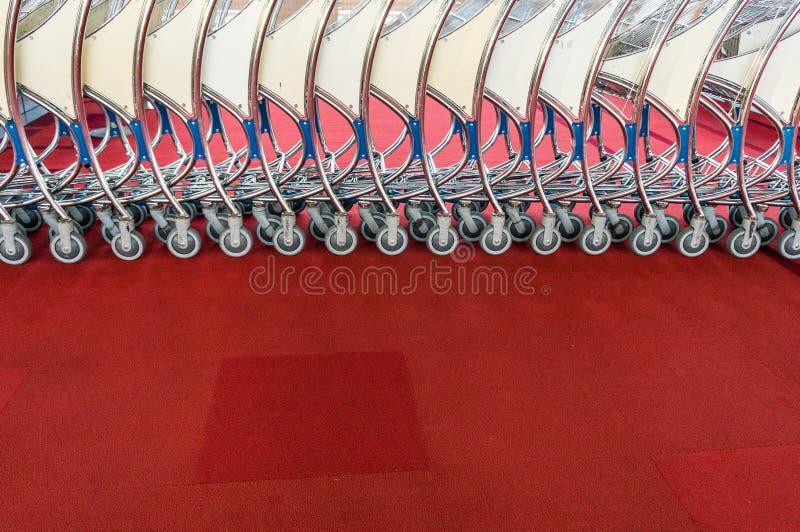 Fila de los carros del equipaje en el aeropuerto moderno fotos de archivo