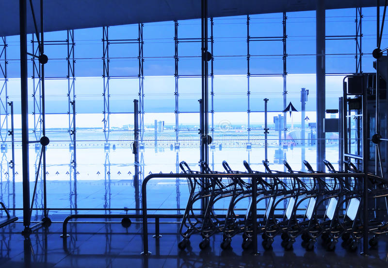 Fila de los carros del equipaje en el aeropuerto ocupado fotografía de archivo