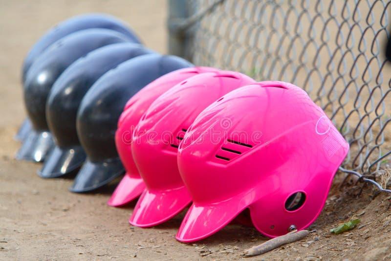 Fila de los cascos del beísbol con pelota blanda de las muchachas fotos de archivo libres de regalías