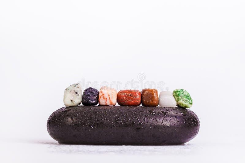 Fila de los cristales de Chakra en piedras calientes del negro del masaje imágenes de archivo libres de regalías