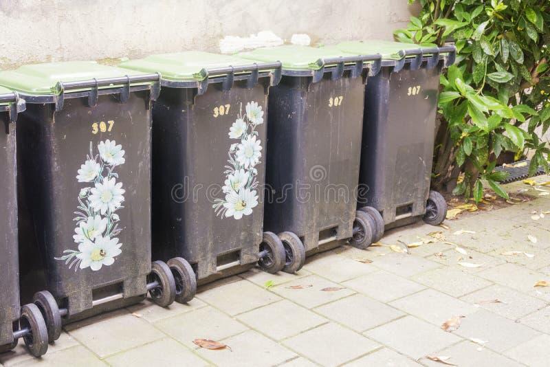Fila de los envases de la basura, algunos adornados para hacerlos hermosos, en la ciudad contra una pared vieja del cemento Una p imágenes de archivo libres de regalías