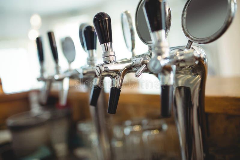 Fila de los golpecitos de la cerveza en el café fotografía de archivo libre de regalías