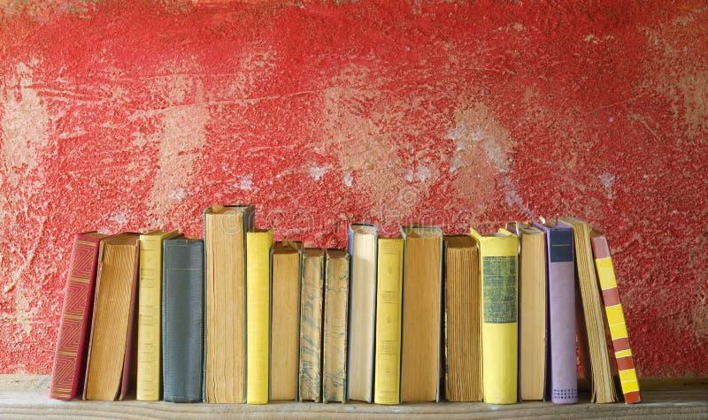 Fila de los libros del vintage en fondo rojo imagen de archivo
