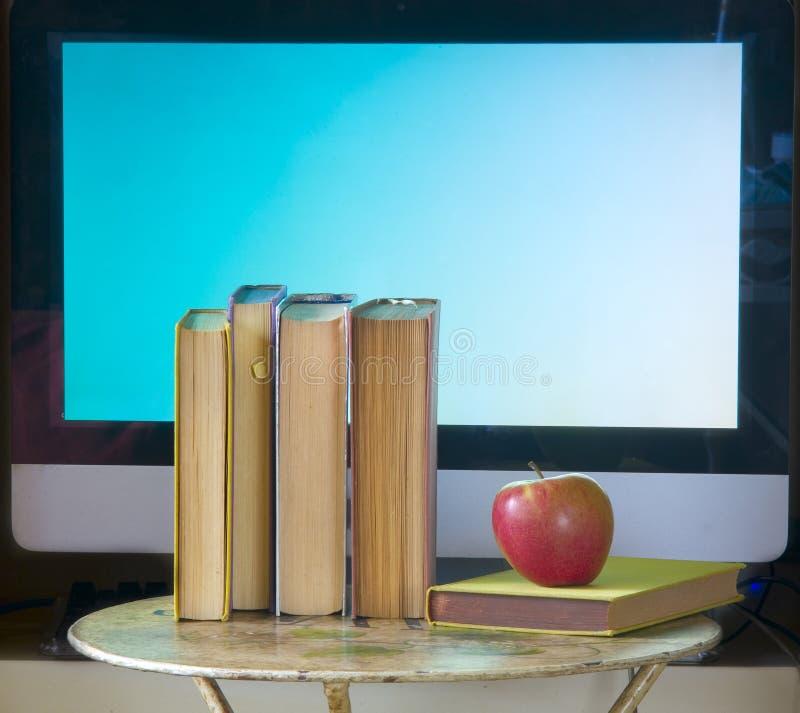 Fila de los libros, una pantalla de ordenador y una manzana, de nuevo a la escuela, aprendiendo, educación imagen de archivo
