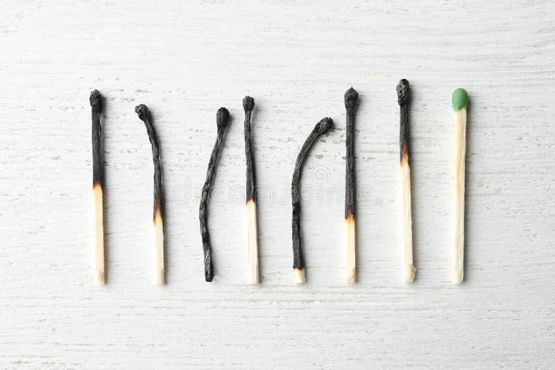 Fila de los partidos y del conjunto quemados uno en fondo de madera Concepto de la unicidad foto de archivo