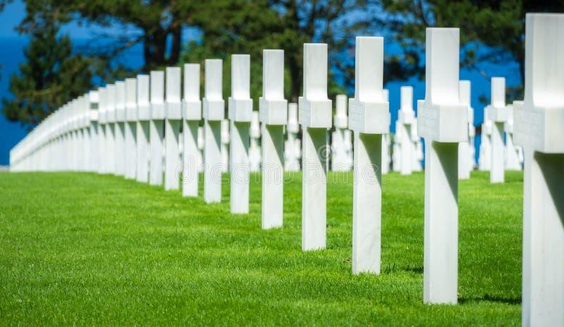 Fila de los sepulcros militares de los E.E.U.U. con las cruces blancas en un grassfield Cementerio americano de Normandía del día foto de archivo libre de regalías