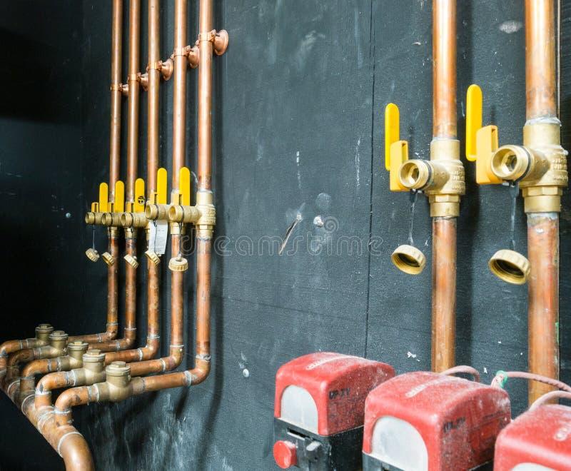 Fila de los tubos y de las válvulas de cobre imagen de archivo
