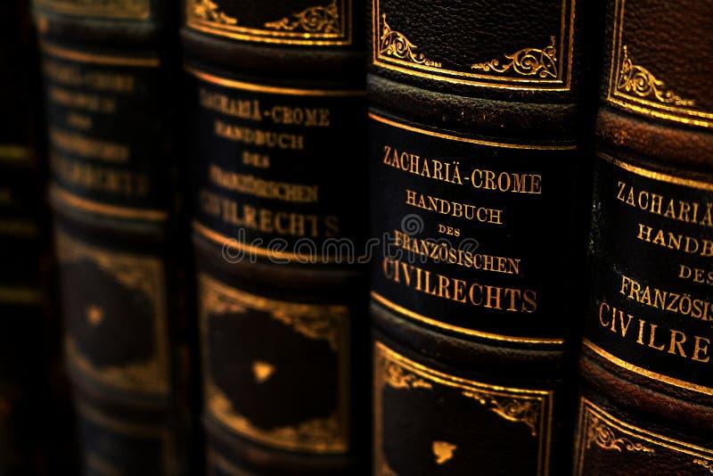 Fila de manuales antiguos sobre el derecho civil francés con las cubiertas de cuero y los títulos alemanes en letras de oro fotografía de archivo libre de regalías