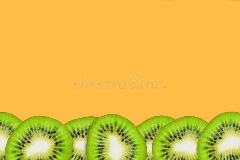 Fila de pedazos de fruta de kiwi fresca madura hermosa sabrosa cortada en la tabla anaranjada en cocina Visión superior Cocinar c fotos de archivo libres de regalías