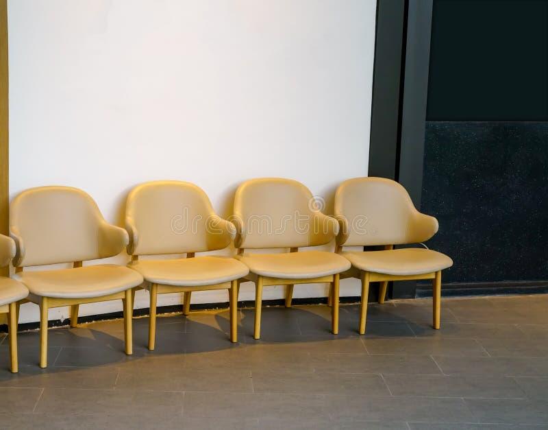 Fila de sillas marrones claras en el vestíbulo Alignme de las sillas de cuero imagen de archivo libre de regalías