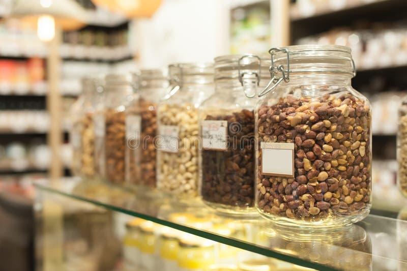 Fila de tarros con los cacahuetes y las semillas en el colmado Bio comida co imágenes de archivo libres de regalías