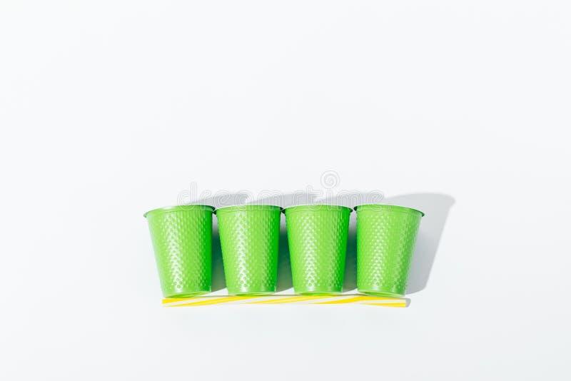 Fila de tazas y de la paja disponibles en el fondo blanco imágenes de archivo libres de regalías