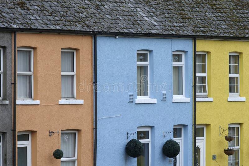 Fila de tres casas brillantemente coloreadas fotos de archivo