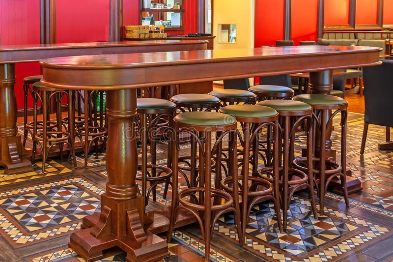 Fila de tronas de madera en una barra delante de una tabla en un pub imagen de archivo libre de regalías