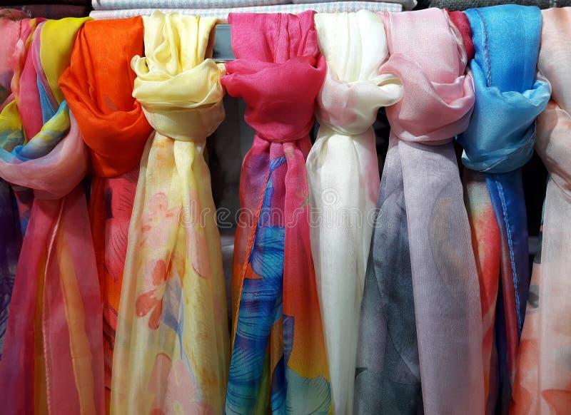 Fila de un woman' coloreado hermoso; las bufandas de s ataron el nudo al estante que colgaba en tienda imagen de archivo