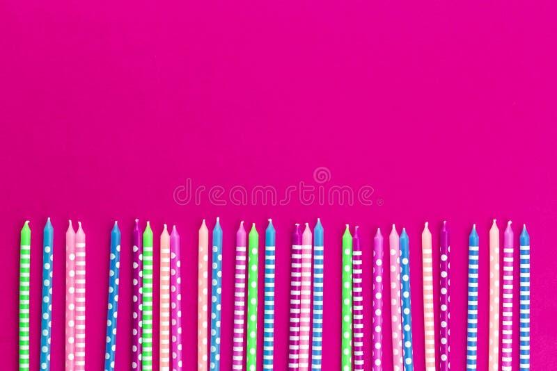 Fila de velas coloridas en el fondo rosado de neón imagenes de archivo