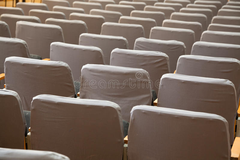 Fila de viejos asientos grises en cine imagenes de archivo