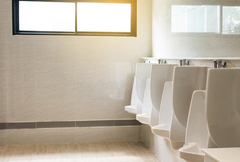 Fila degli orinali bianchi dell'interno per l'uomo nella toilette, lavabo di lusso moderno di progettazione immagine stock libera da diritti
