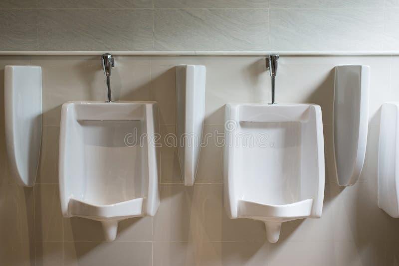 Fila degli orinali bianchi dell'interno per l'uomo nella toilette, lavabo di lusso moderno di progettazione immagini stock