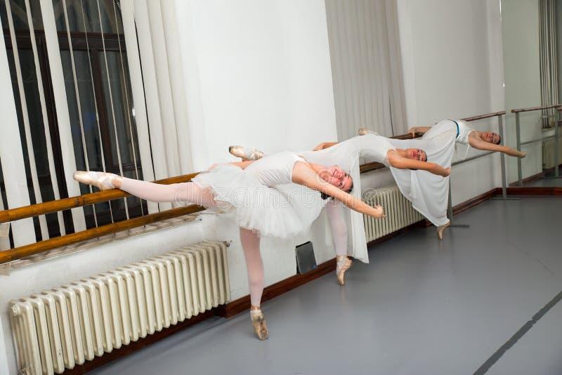 Fila dei ballerini di balletto che praticano alla sbarra nella stanza di ripetizione fotografia stock