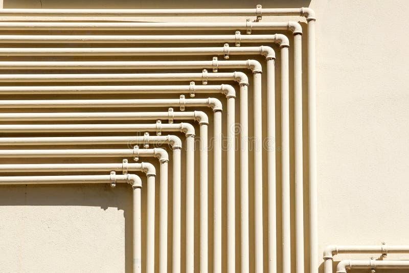 Fila dei contatori del gas naturali con i tubi gialli sul muro di mattoni della costruzione immagine stock libera da diritti