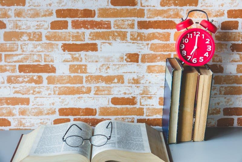 Fila dei libri e della sveglia rossa con i vetri dell'occhio sul libro aperto fotografia stock