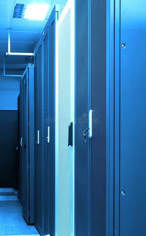 Fila dei mazzi chiusi degli scaffali con i server ed i router in grande centro dati con la tonalità blu al neon Internet potente fotografia stock libera da diritti
