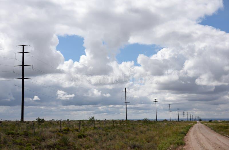 Fila dei pali di elettricità ed e delle linee elettriche ad alta tensione in un paesaggio rurale con cielo blu e le nuvole immagini stock libere da diritti