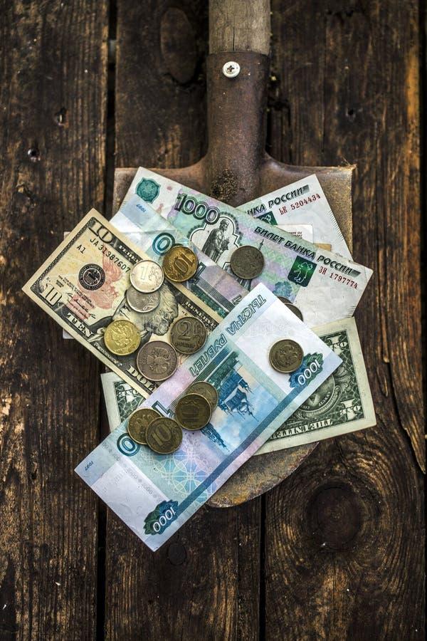 Fila dei soldi con una pala immagini stock libere da diritti
