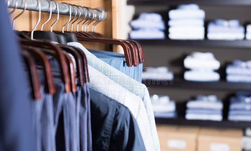 Fila dei vestiti sui ganci fotografia stock