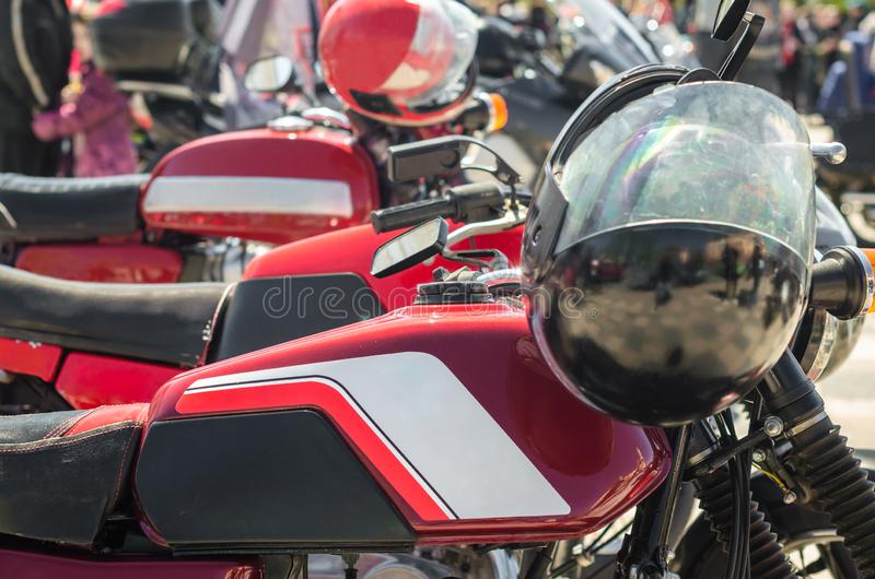 Fila del corredor rojo de los cafés de la motocicleta del vintage con los cascos en competencias imagen de archivo