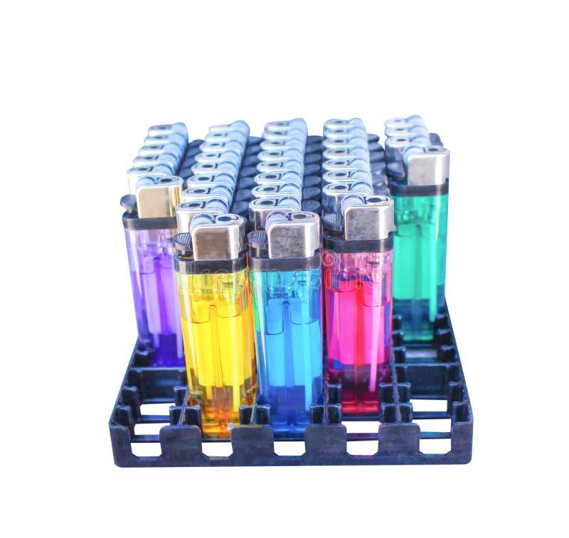 Fila del encendedor de gas multicolor en el paquete negro aislado en el fondo blanco con la trayectoria de recortes fotos de archivo