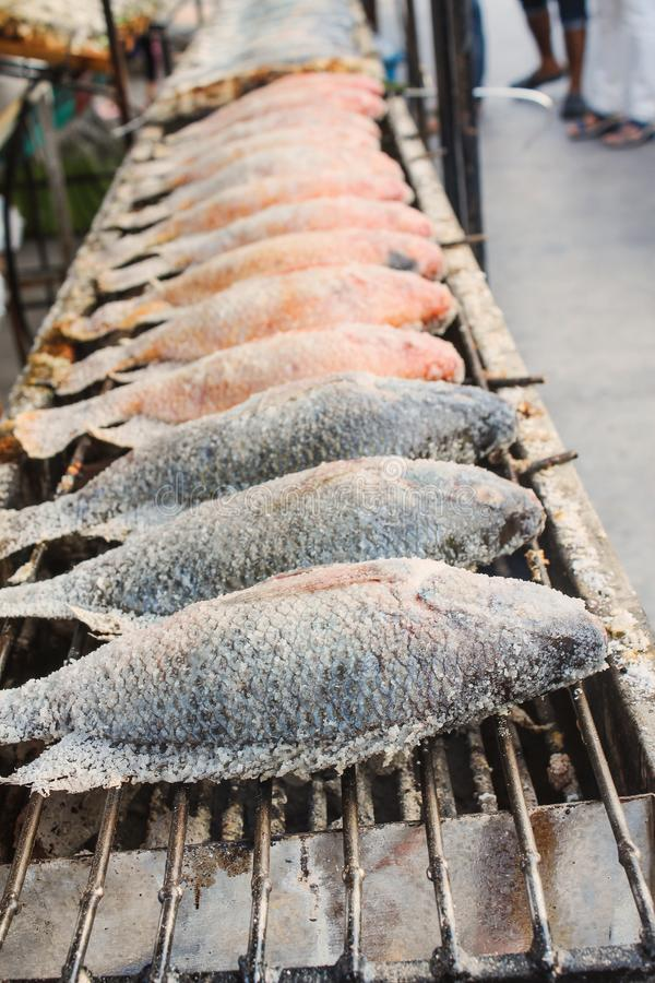 Fila del pesce arrostito con sale sulla griglia del carbone nel mercato locale Nile Tilapia Fish, pesce rosso di tilapia immagine stock libera da diritti