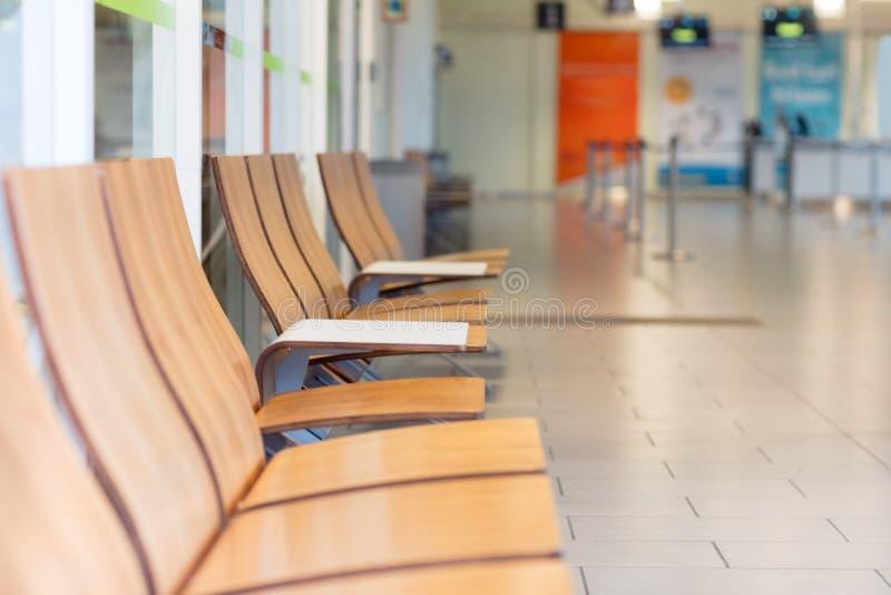 Fila della sedia di legno nella sala di attesa all'aeroporto immagine stock libera da diritti