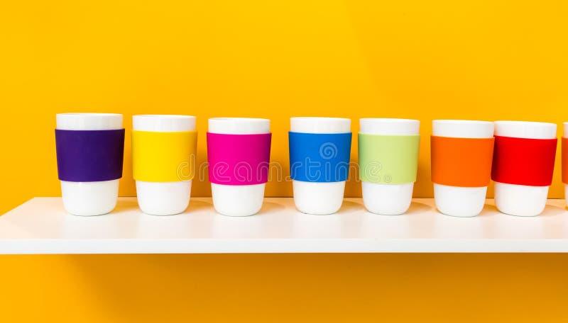 Fila della tazza ceramica bianca con la tazza variopinta del silicone di pantone immagini stock libere da diritti