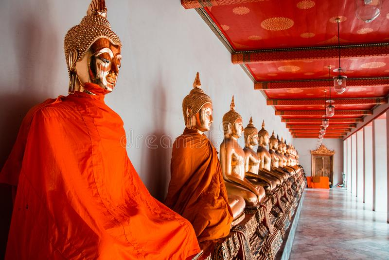Fila delle figure di seduta statue di Buddha di meditazione dorata in tempio di Wat Pho a Bangkok immagini stock libere da diritti