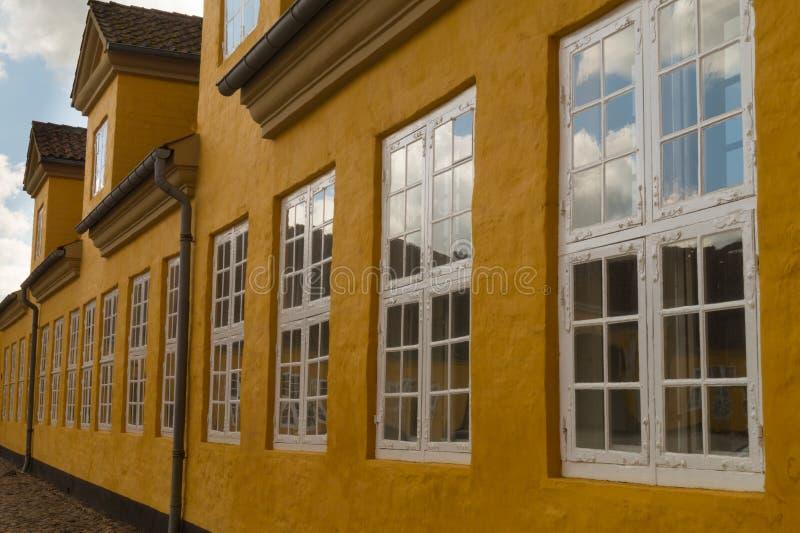 Fila delle finestre della stoffa per tendine sulla casa gialla immagini stock libere da diritti
