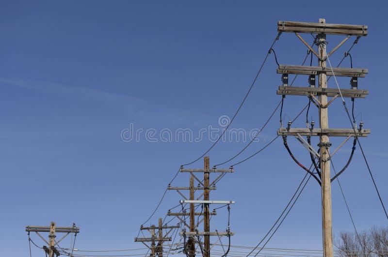 Fila delle linee dell'alimentazione elettrica e dei pali pratici contro un cielo blu immagine stock libera da diritti
