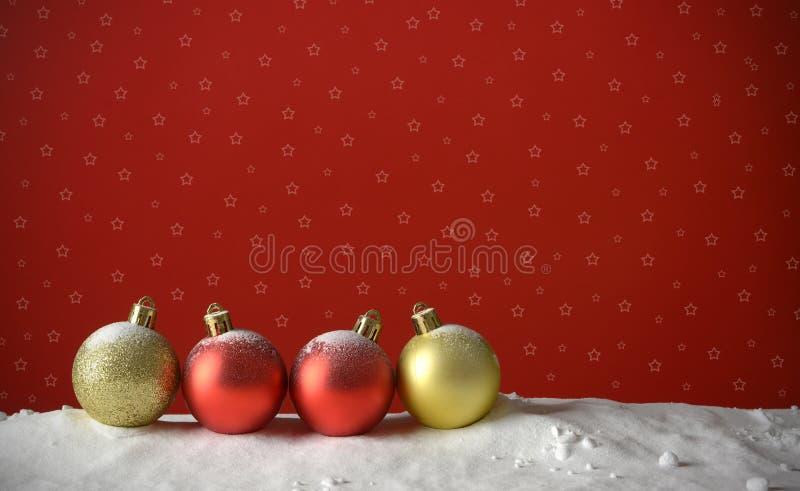 Fila delle palle di Natale sulla neve e sui precedenti rossi immagini stock