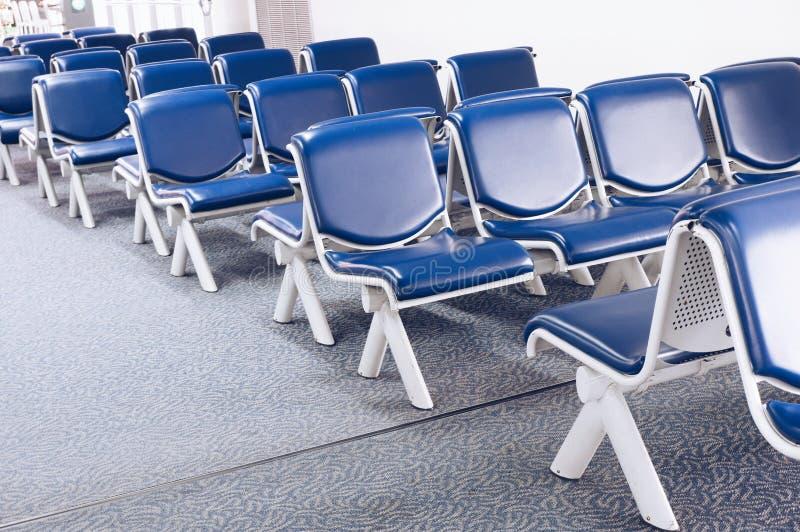 Fila delle sedie blu nell'aeroporto alla zona diretta all'estero molto pulita ed all'ordinazione fotografie stock