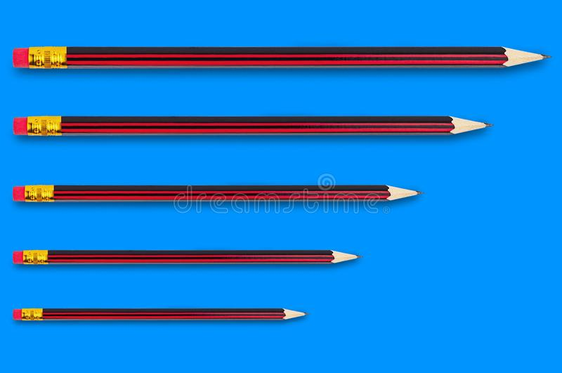 Fila di nuove matite di legno della grafite con la punta della gomma di gomma su fondo blu fotografia stock libera da diritti