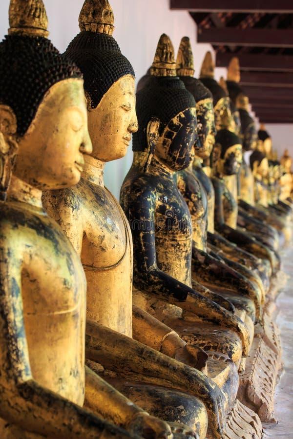Fila di vecchia statua dorata di Buddha fotografie stock