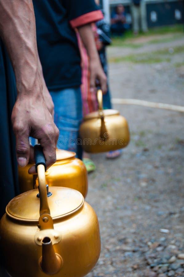 Fila dos povos com potenciômetro dourado à disposição fotografia de stock royalty free