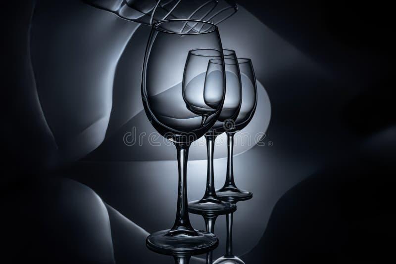 fila en las copas de vino de lujo vacías, oscuras imágenes de archivo libres de regalías